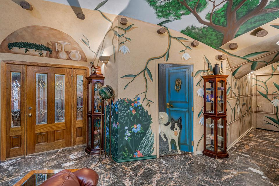The front door, a hallway, and the door to the pantry feature whimsical murals.