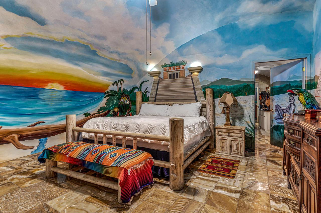 An intense sunset is painted on the dome wall of this bedroom.